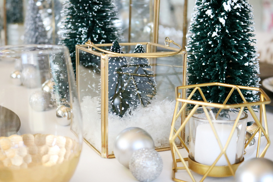 Simple and Modern Christmas Dining Table Ideas - BHG Live Better Gold Lanterns filled with mini bottle brush trees and fake snow