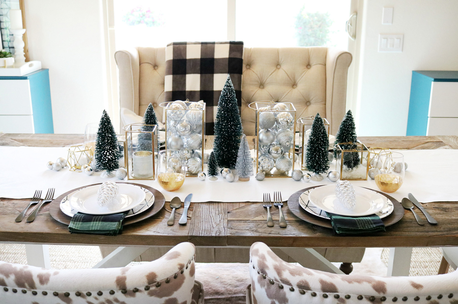 Simple and Modern Christmas Dining Table Ideas - Traditional decor easily becomes simple and modern with geometric plates, mixed metallics, and modern touches like black silverware paired with gold dipped stemless wine glasses.