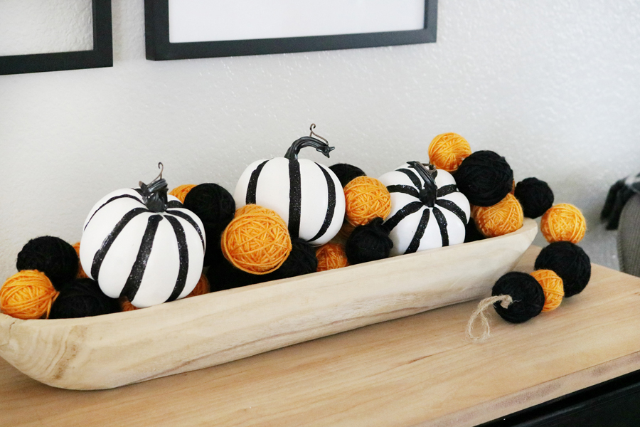 Simple Black & White Halloween Decor - Grab a decorative wood bowl and fill it with cute pumpkins and a textured garland.