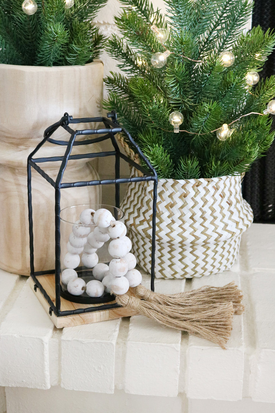 Black & White Casual Boho Christmas Decor - Fill lanterns with wooden casa beads and twinkle lights.