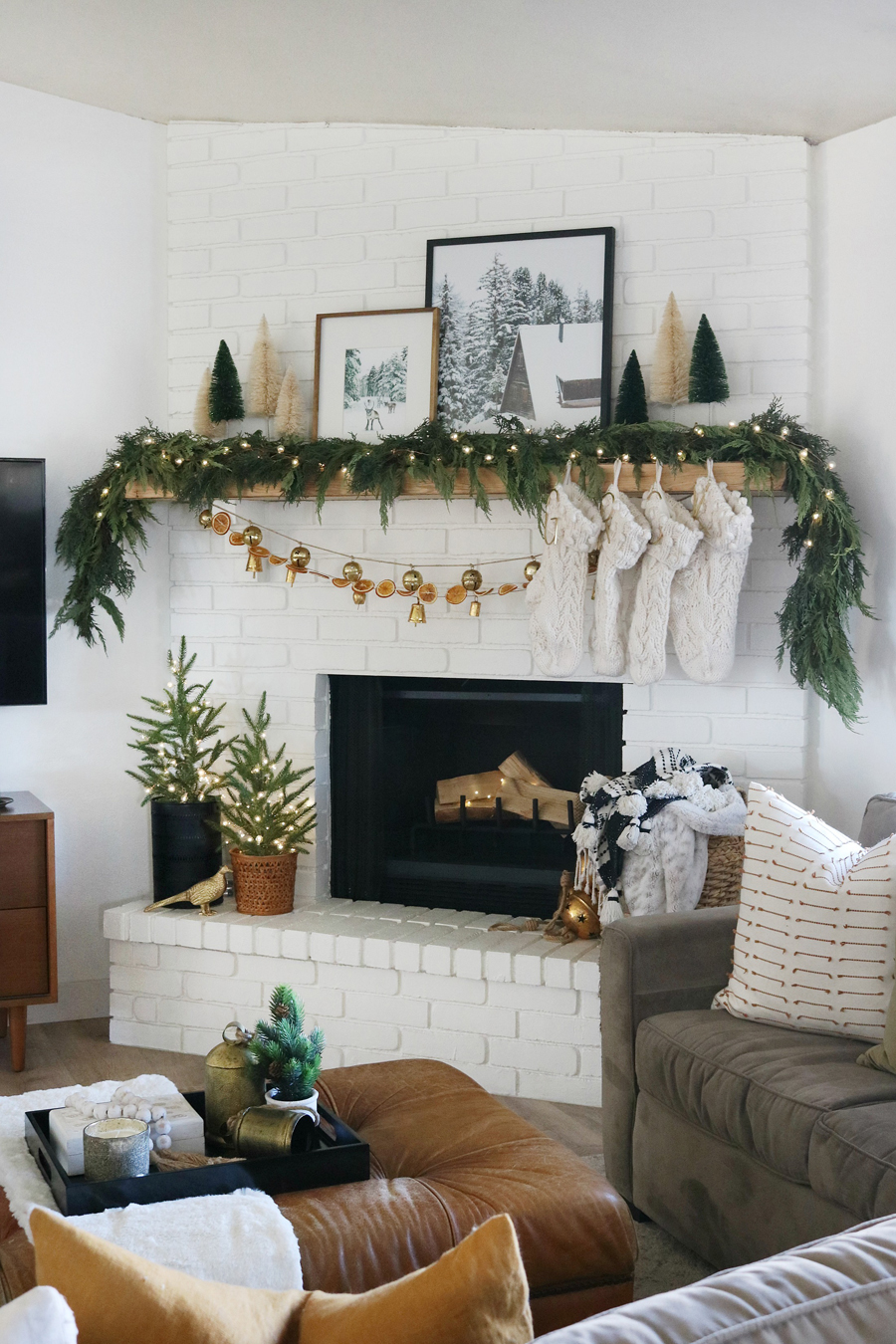 Create a Cozy and Modern Holiday Look with Live Green Garlands, Dried Orange Slices, Neutral Decor, and Touches of Metallic Golds.